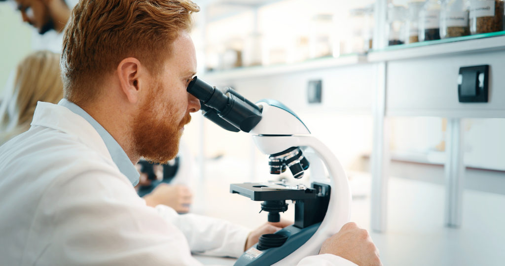 Male doctor looking through a microscope